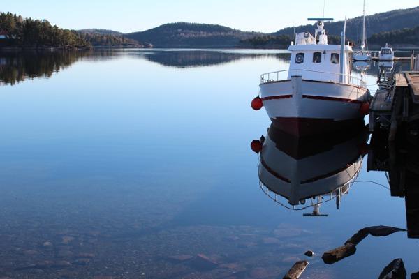 Speilblank sjø med fiskebåt ved brygga