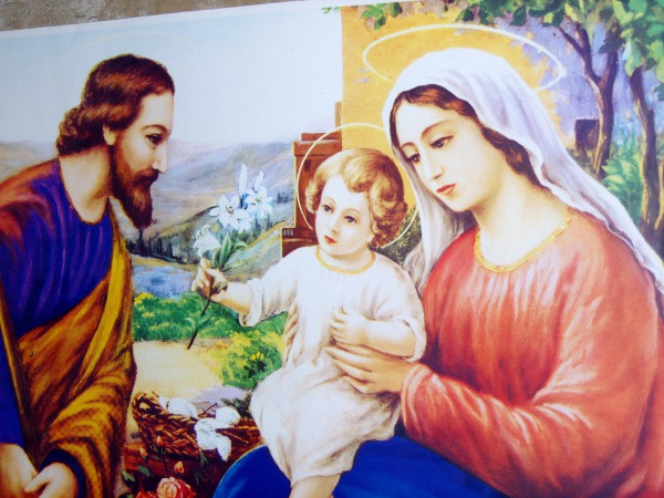 Plakat av Maria, Josef og Jesusbarnet som holder en hvit lilje