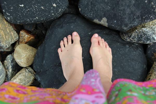 Barføtt på svart stein i fjæra