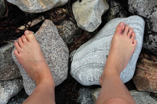 Barføtt på store steiner i fjæra